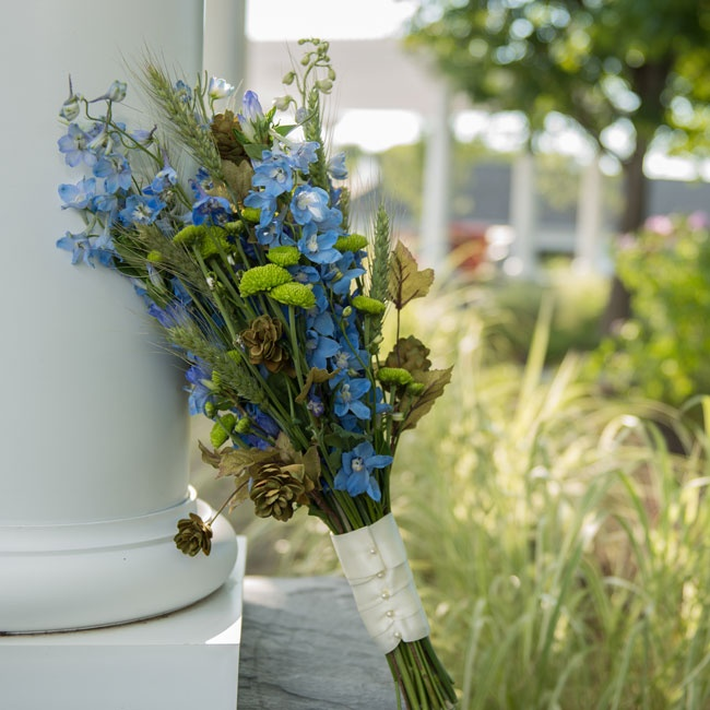 Tracy carried a bouquet filled with bright blue wildflowers and green mums mixed with rustic elements like wheat and dried leaves.