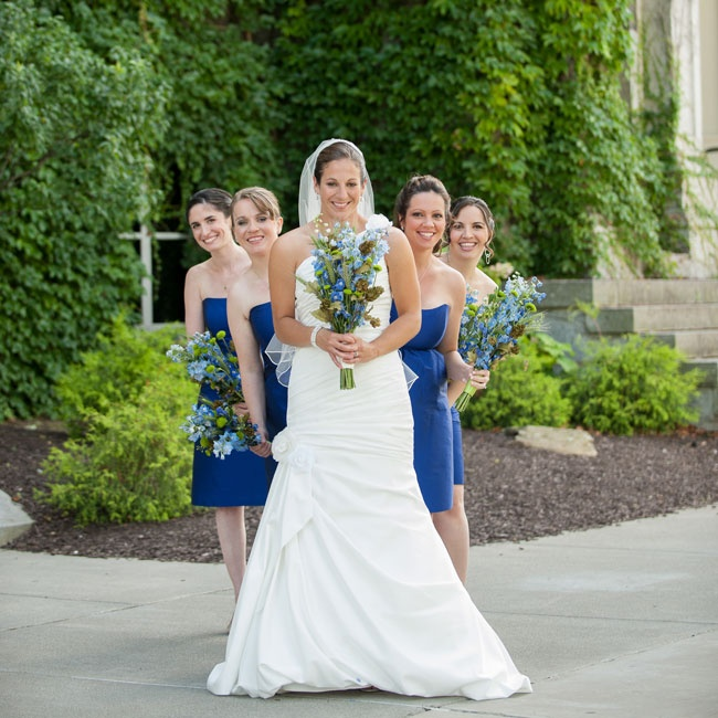 Tracy's bridesmaids wore short strapless dresses in a bright cobalt blue, which perfectly complemented their bouquets, a mix of blue delphiniums and rustic elements.