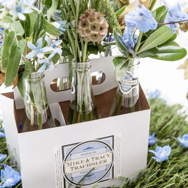 Some of the reception tables featured customized carrying cases filled with simple bundles of blue delphiniums and rustic details in clear glass bottles.