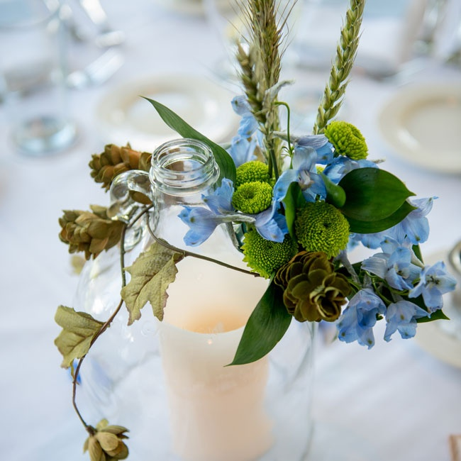Glass bell jars covered arrangements of wildflowers and moss, providing unique focal points for the tables.
