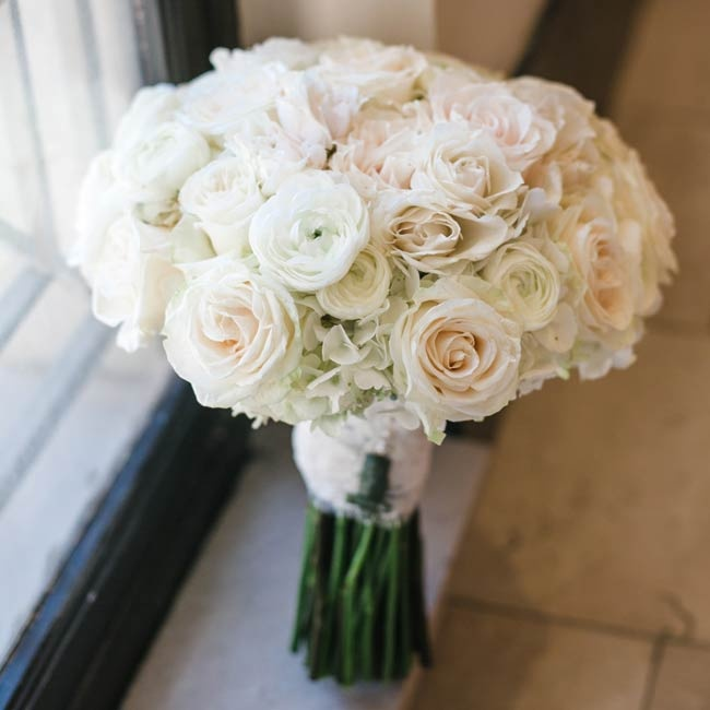 The bride carried this bouquet of white ranunculuses, roses and hydrangeas down the aisle.