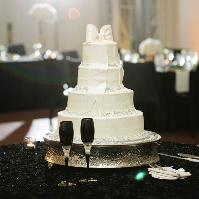 The couple's cake had four tiers and a white bow made of fondant sat on top.