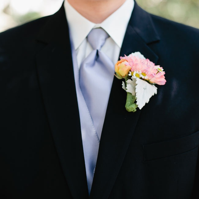 Groomsmen wore traditional black tuxes with purple satin vests and ties and matching soft pink boutonnieres.