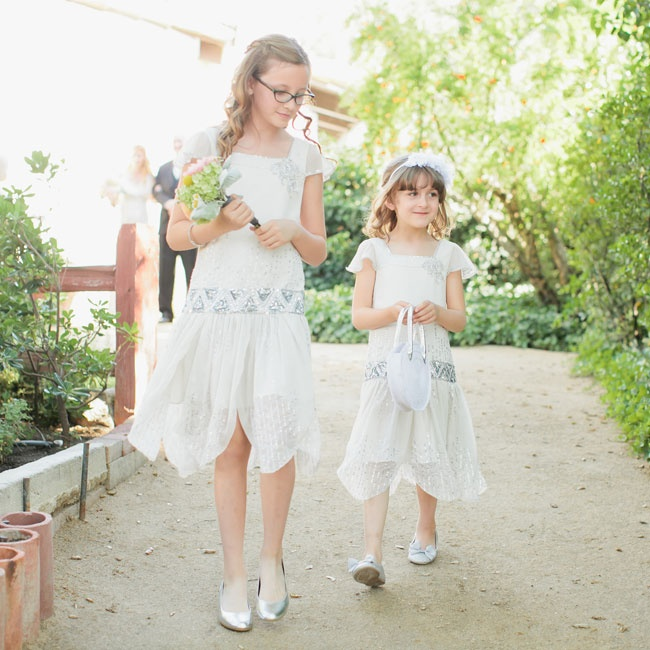 The flower girls wore 1920s-inspired, drop-waist, glam garb for the outdoor ceremony.