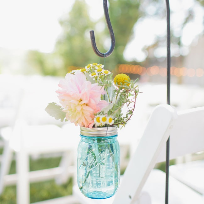 The couple decorated their ceremony aisle with bright blue Mason jars filled with pale flowers.