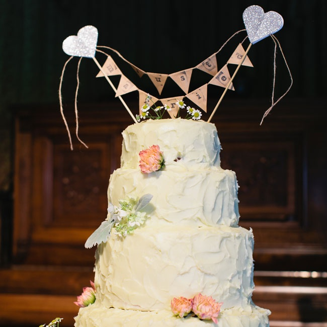 "The bride and groom chose a rustically frosted, tiered, round cake and topped it with pennants that spelled out, ""Just Married."""