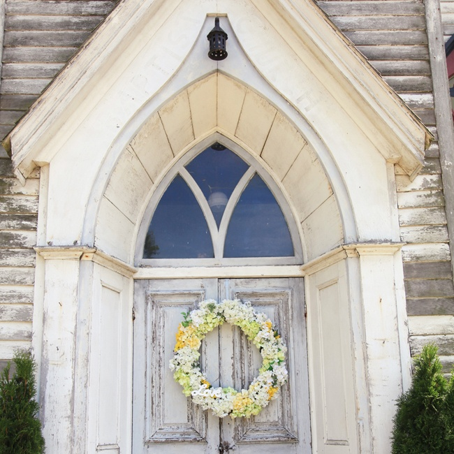 The rustic church doors displayed cheerful floral wreaths in shades of yellow, green and white.
