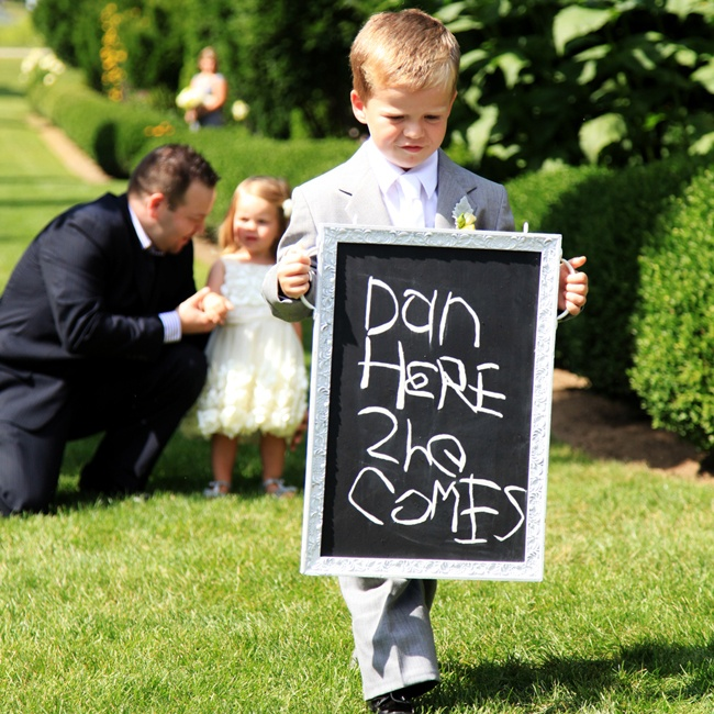 A younger member of the bridal party announced the arrival of the bride as he walked down the aisle carrying a chalkboard sign.