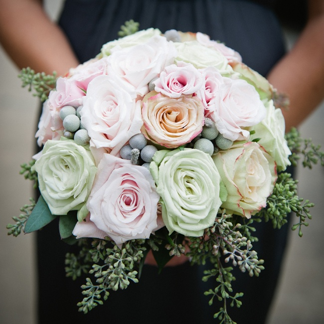 Silver brunia berries peeked out between the lush petals of the pastel-color roses in the bridesmaid bouquets.