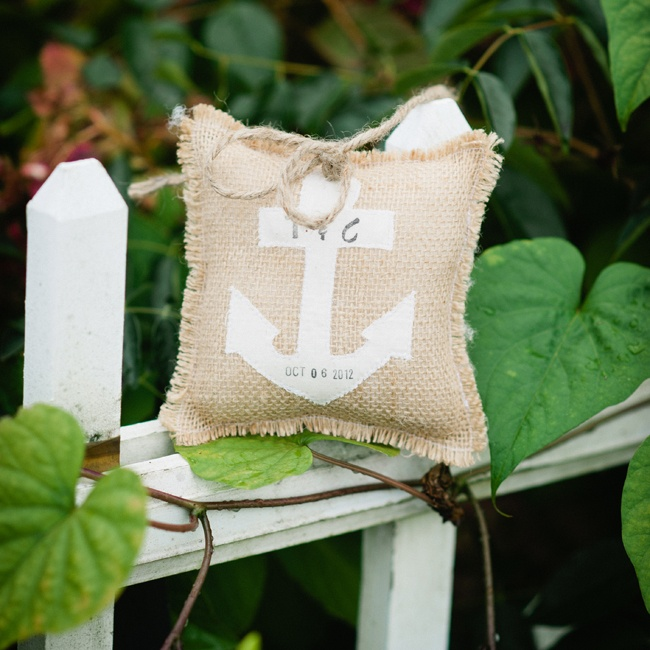 The ring pillow was made from burlap and had a white anchor design for a nautical look. The couple's initials and wedding date were stamped on the anchor.