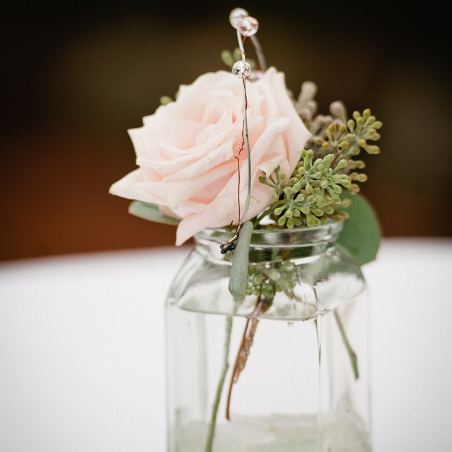 Single rose buds and seeded eucalyptus were placed in vintage-style apothecary jars for simple, romantic look.