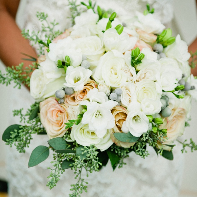 """We chose flowers that would match the theme—cream, white, pink and gray—and wrapped everything in burlap for a rustic, romantic touch,"" Tina says. She carried cream and ivory roses, white freesia, gray brunia berries and seeded eucalyptus in her bouquet. The centerpieces had hydrangeas, roses, brunia berries and eucalyptus."