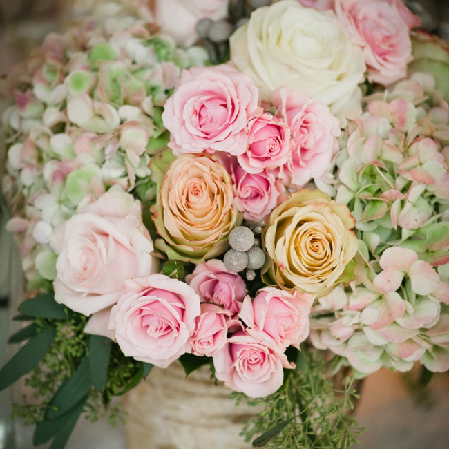 Hydrangeas, roses and brunia berries were placed in rustic birch vases on the guest tables.