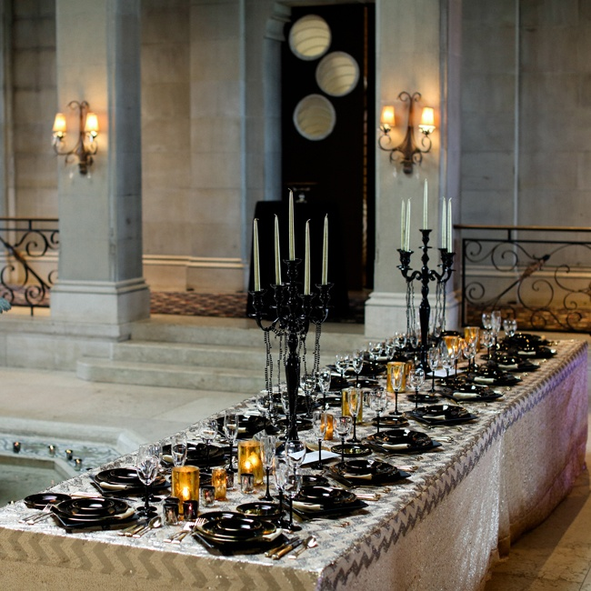 For the table decorations, there were black chandelier candles with black pearls hanging from them and tablecloths made of black and gold sequins. The silverware was gold as well and candles covered the tables.