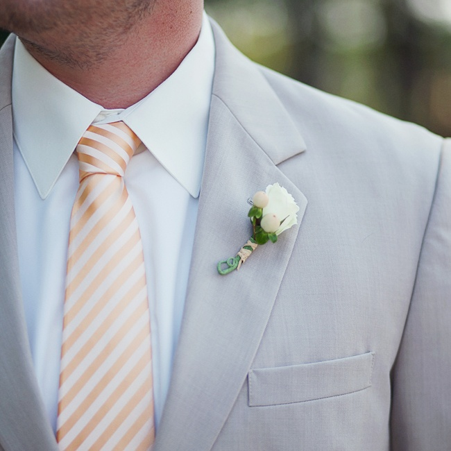 Each of the groomsmen wore an ivory rose boutonniere accented by cream-colored hypernicum berries.