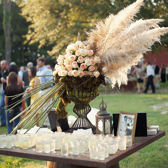 Extravagant floral arrangements like this one decorated with large feather-like plants and a mountain of ivory and blush roses brought an element of drama to the reception decor.