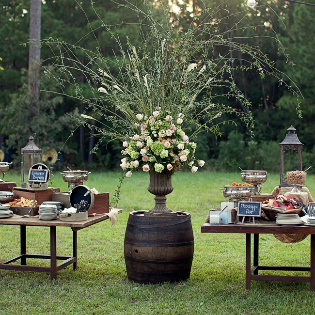A buffet with a mix of classic Louisiana and Mississippi inspired snacks were arranged on long farm tables. A lavish, layered floral arrangement displayed on an old wine barrel added a rustic feel to the reception decor.