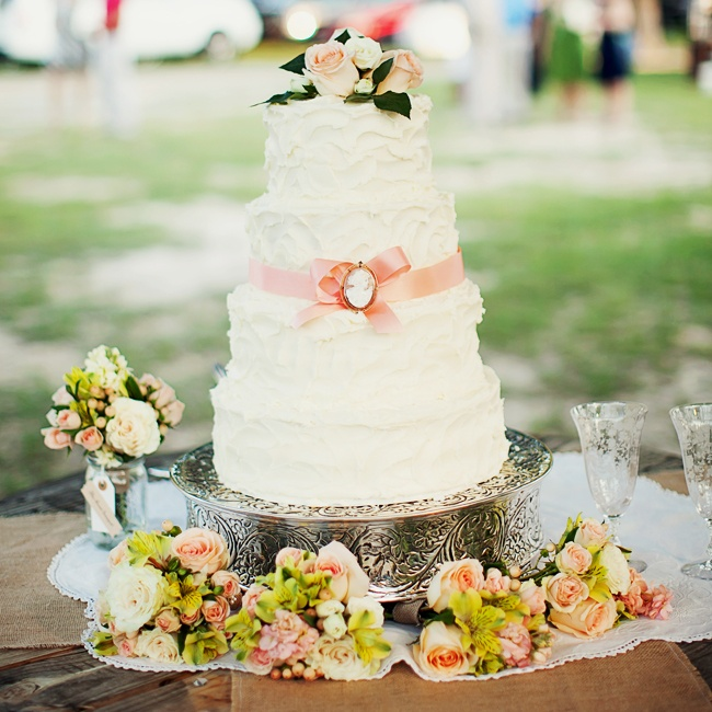 The four-tiered buttercream cake was accented by a single pink ribbon gathered into a bow that was embellished with a Victorian-inspired charm. The cake was topped with a fresh bunch of pale pink roses and was displayed on an ornately decorated pewter cake stand.