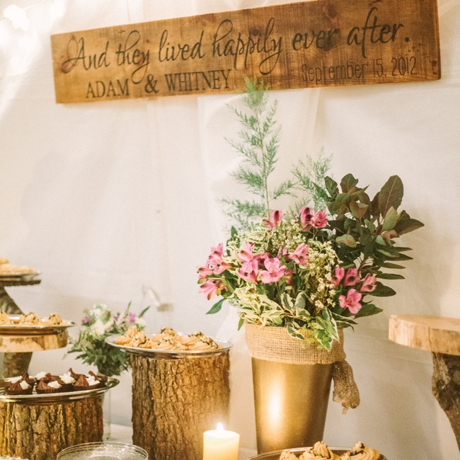 Adam's cousin gifted the couple a hand-painted wooden sign with their names and wedding date, which hung above the dessert table. Log serving tiers made by Whitney's dad and vintage cake stands from grandmothers on both sides held various tarts and mini pies.