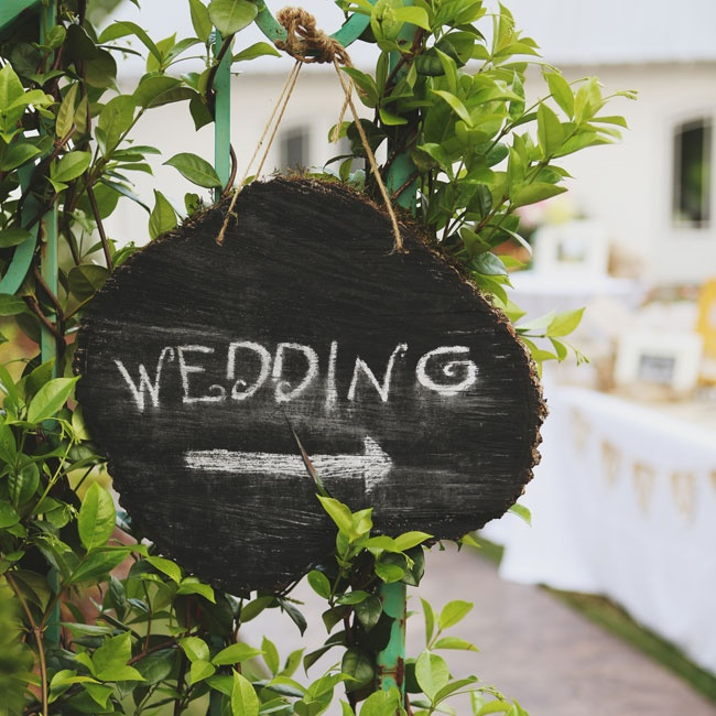 The couple made this DIY chalkboard to point out their ceremony location out of a tree slab and chalkboard paint.