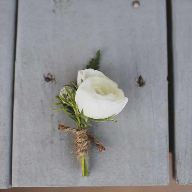 White ranunculus boutonnieres were wrapped in rustic brown twine for the ceremony.