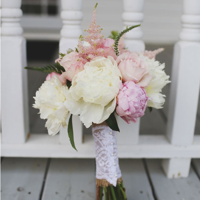 The bride carried a bouquet of soft pink peonies wrapped in lace down the aisle.