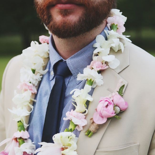 The groom wore this traditional Hawaiian lei of orchids along with his pink ranunculus boutonniere.