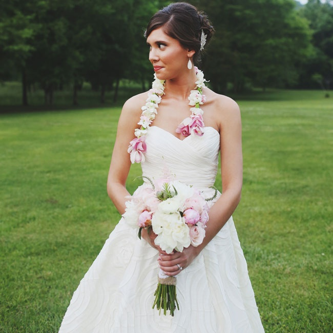 The bride wore this traditional Hawaiian white lei with pink accents as an accessory to her strapless, A-line dress.