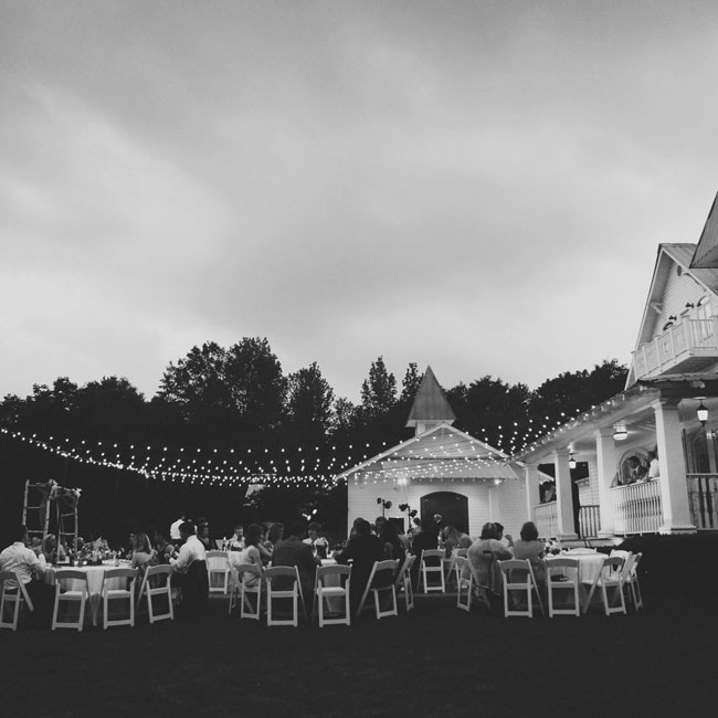 Guests were arranged in round tables under cafe lights just outside the main house at the reception venue.