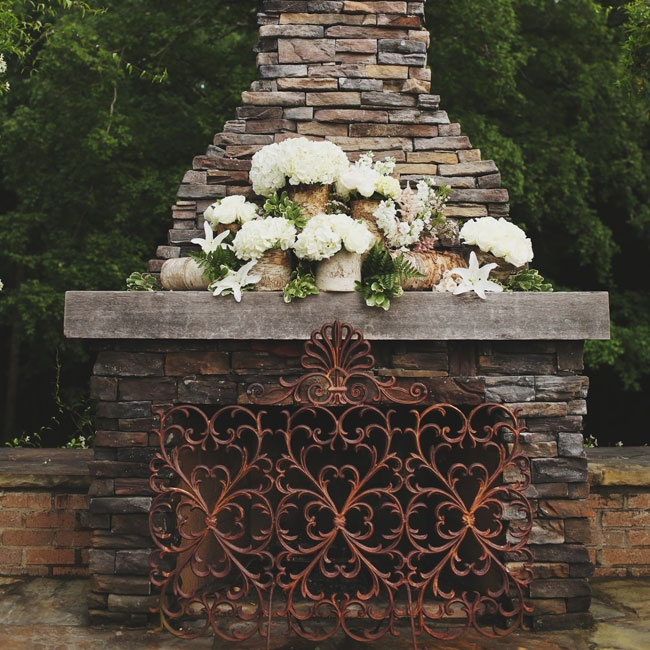 An outdoor fireplace with an ornate grate and a large assortment of flowers provided a rustic background for the outdoor celebrations.