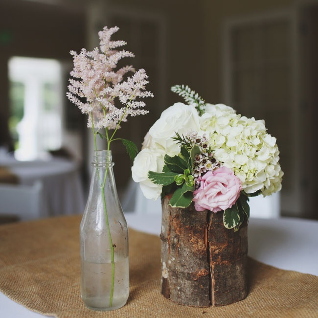 Blooms of hydrangeas and roses filled antique bottle and rustic wooden centerpieces at the reception.