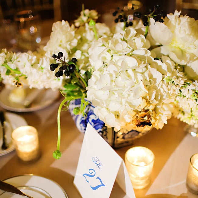 Bunches of white hydrangeas and lilac were arranged in floral blue and white porcelain vases. Simple white tent cards with royal blue ink marked each table.