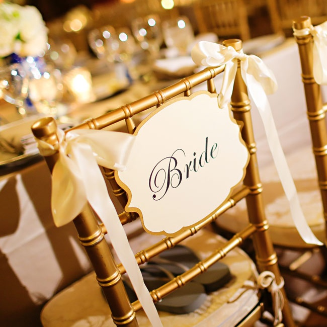 "Allison and Brandon's gold chiavari chairs were decorated with simple cream and gold signs reading ""Bride"" and ""Groom."""