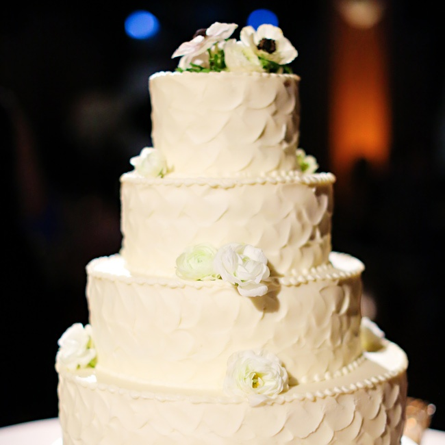 The four-tiered buttercream cake was frosted in a scalloped, petal-like pattern and dotted with delicate white flowers.