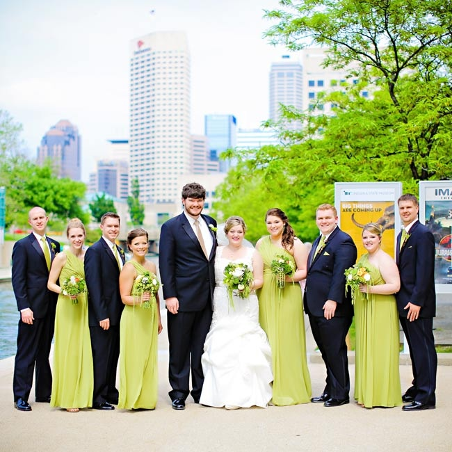 Brittany's bridesmaids wore floor-length chiffon gowns with a one-shoulder asymmetric neckline in a bright peridot green color. The groomsmen wore classic black suits and peridot ties that complemented the girls' dresses.