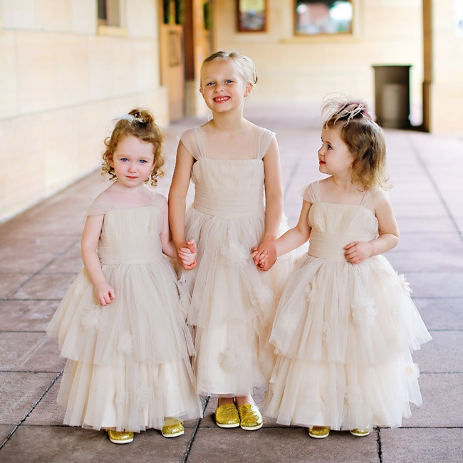 The flower girls wore layered tulle dresses in a neutral color and glitzy gold Tom's shoes.