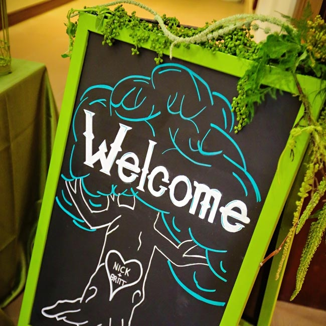 The couple welcomed guests with a green-framed chalkboard sign that was decorated with amaranthus.