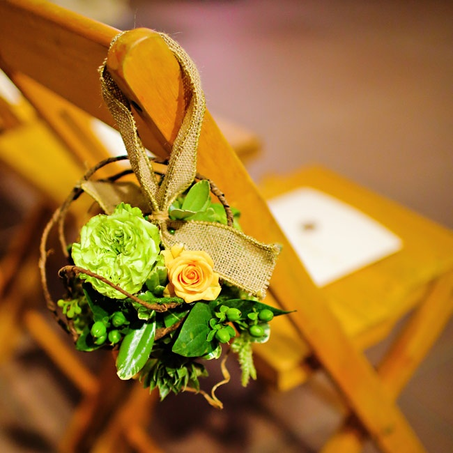 Green floral pomanders accented with vines hung from burlap ribbon, marking each of the ceremony aisles.