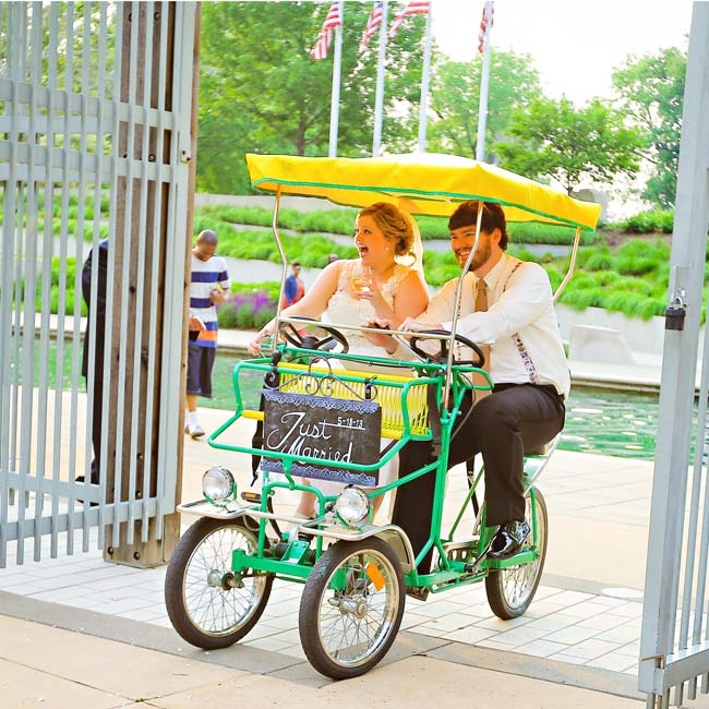 "The couple wheeled around the cocktail hour in a rented single Surrey Bike from Wheel Fun that had a chalkboard sign saying ""Just Married."""
