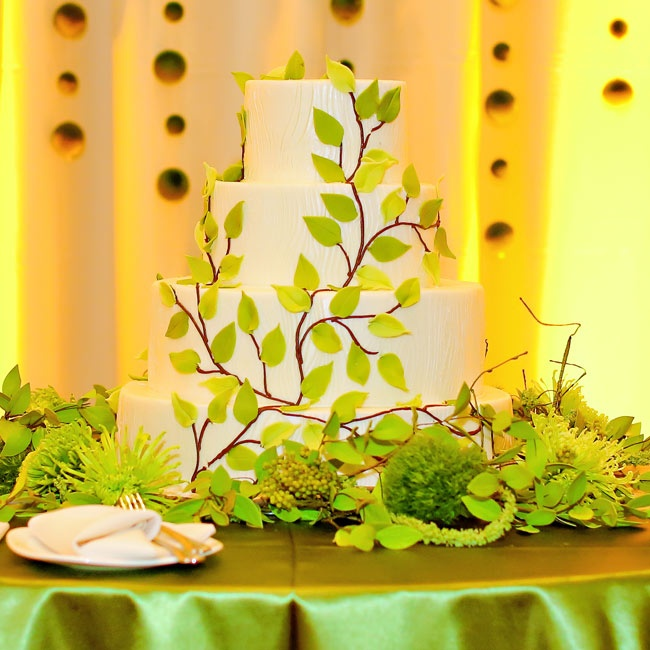 The four-tiered cake was surrounded by a display of lush greenery and was covered in a layer of fondant that was decorated to look like wood. Leafy fondant vines crept up the sides of the cake, complementing the woodland theme.