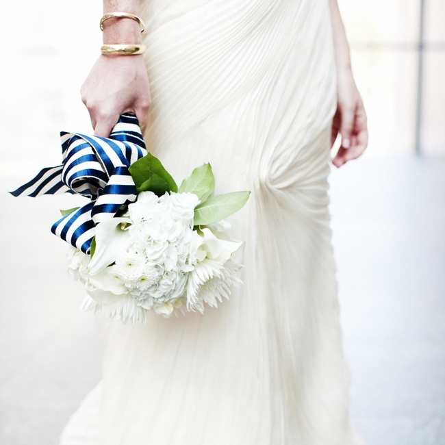 A pure white bouquet of dahlias and hydrangeas was wrapped in a striped navy bow for the bride.