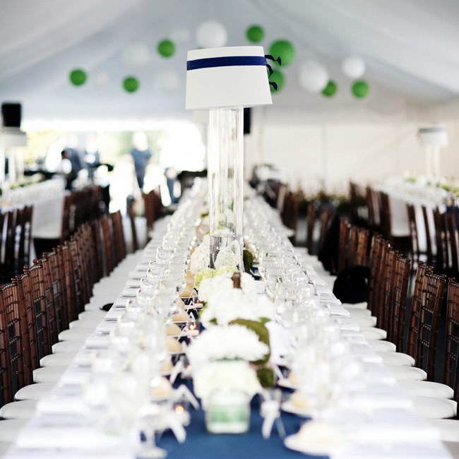 The reception tent had long, elegant tables set in white with darker chairs and white and navy centerpiece.