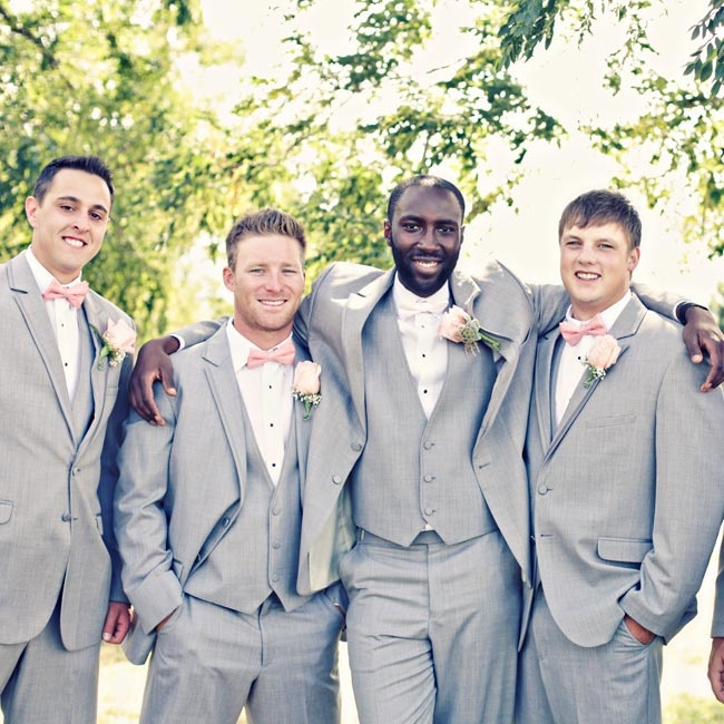 Groomsmen wore light gray three-piece suits from Jos. A. Bank and accessorized with pink bowties.