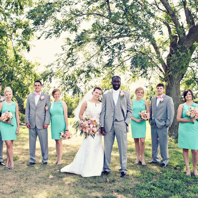 The mint and gray colors of the wedding party perfectly complimented the soft pink floral arrangements.