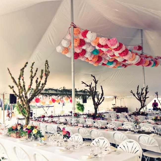 The tented reception space was both colorful and whimsical with large branch-like centerpieces covered in moss and a vibrant, floral rosette canopy.