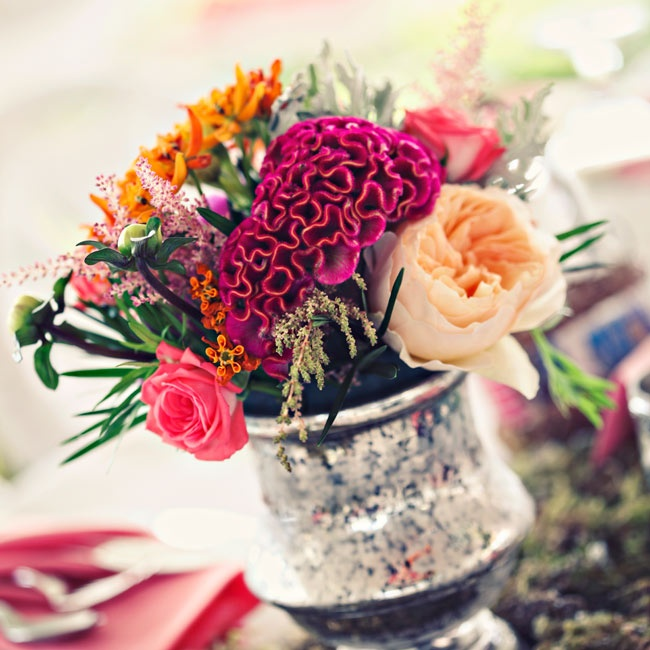 Mercury glass vases were filled with textured bright blooms including pale orange peonies, pink roses and vibrant fuchsia coxcomb.