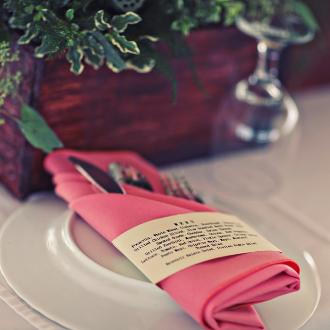 Dinner places were set with an overturned white plate and vibrant pink linen napkins filled with silverware.