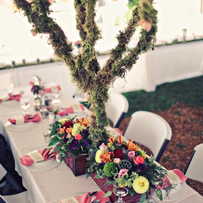 Unique, moss-lined tree branches made for statement-making centerpieces surrounded by low boxes of bright blooms.