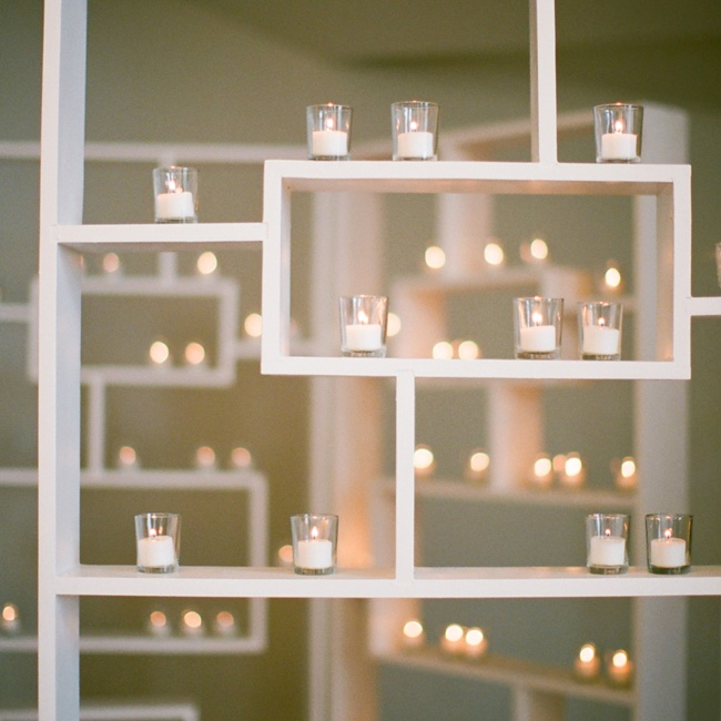 """Mi Mi Design created a wall of candles on the dance floor,"" Bridget says. ""Since we used a DJ instead of a band, we wanted something at the front of the stage, so it wouldn't be wasted space. The white shelving with dozens of votive candles was a perfect solution."