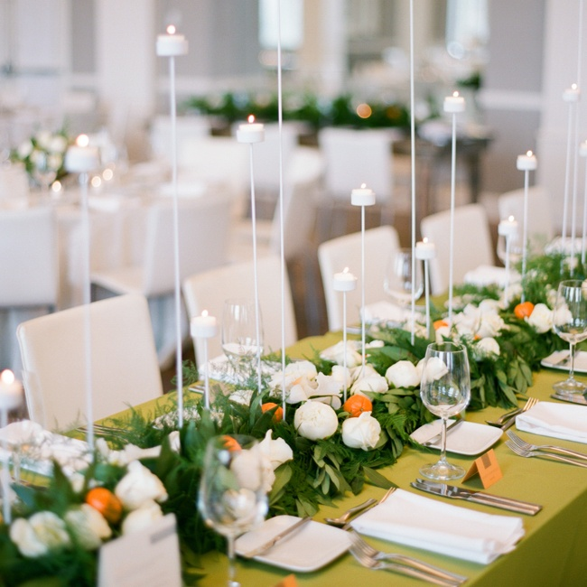 """I knew that all white with greenery would look washed-out in our space, as we were primarily using white tablecloths,"" Bridget says. After talking with Mi Mi Design, they decided on a long, green garland of with loads of white flowers, interspersed with clementines for some color, for the tops of the longer tables. ""Orange is my favorite color, an ..."